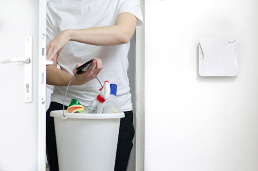 Cleaner entering apartment with phone in hand