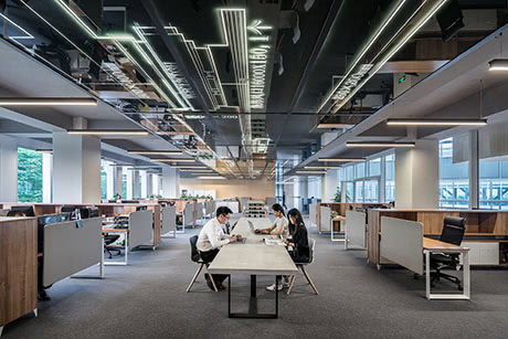 People sitting at a long desk in open space office